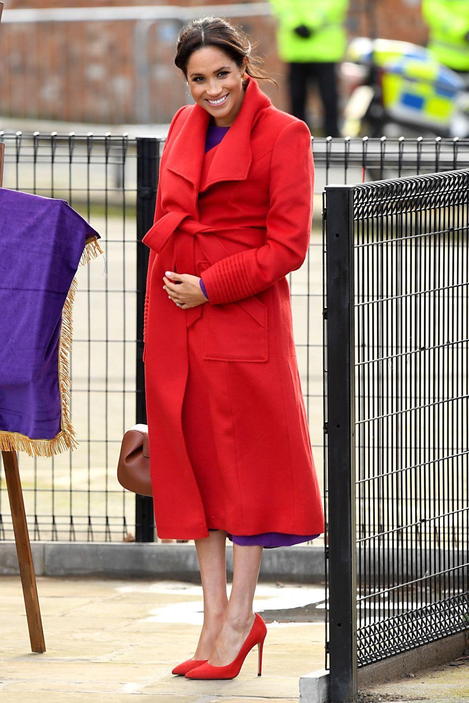 Meghan Markle en Birkenhead con un abrigo rojo.