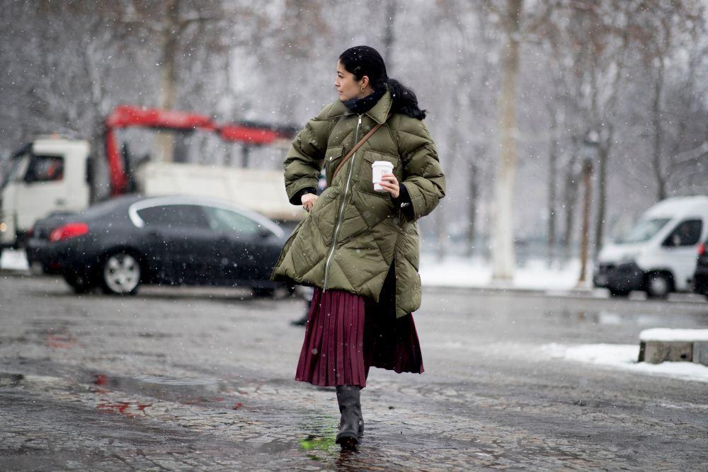 Carolina Issa con plumas, falda midi y botas.