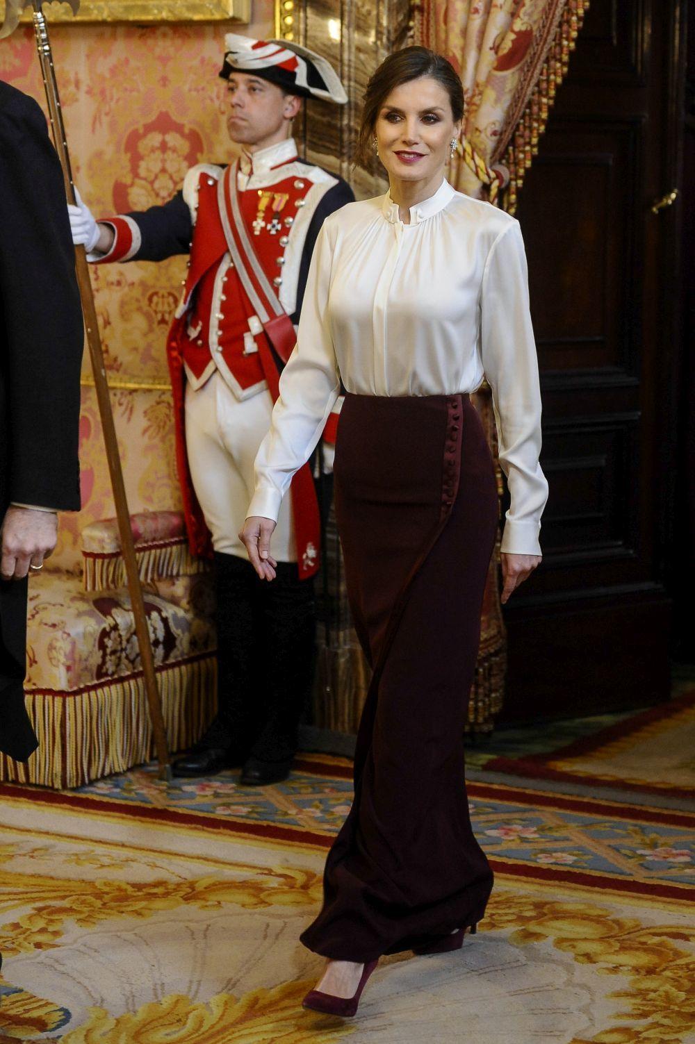La reina Letizia con camisa blanca y falda larga en color burdeos.