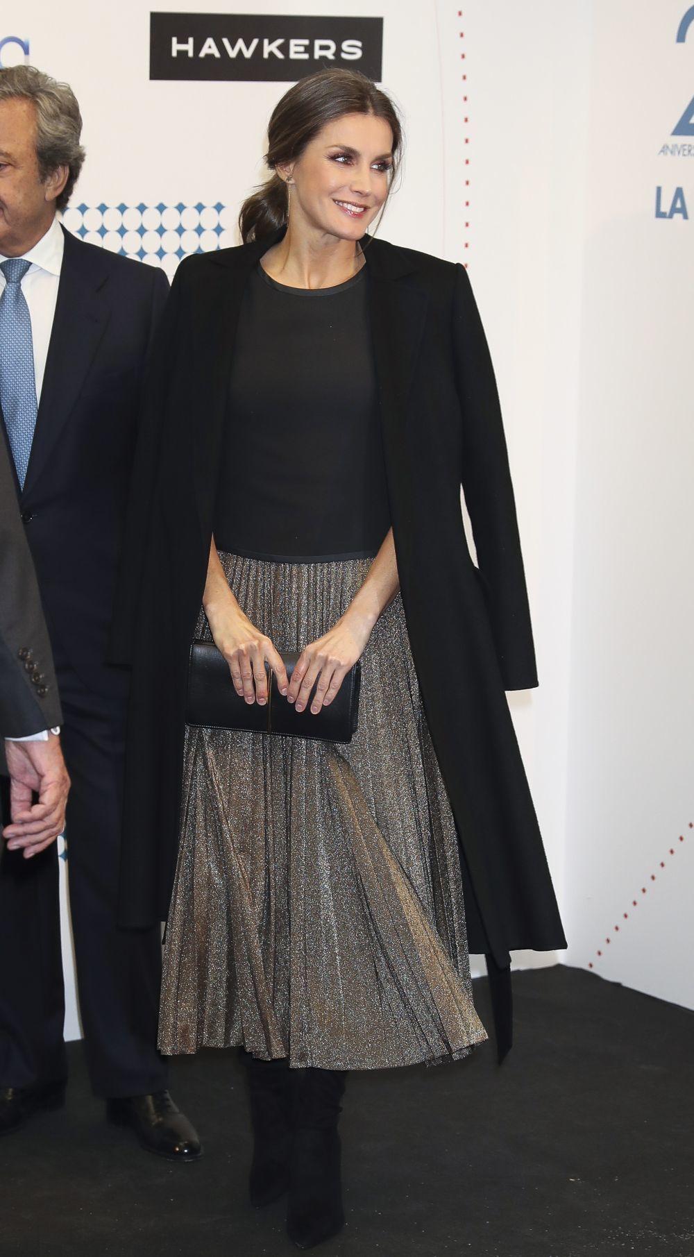 La reina con una sencilla camiseta negra y una falda plisada en color...