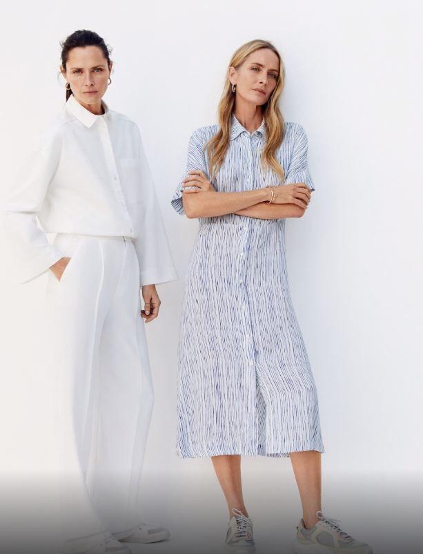 Tasha Tilberg con pantalón y camisa blancos y Georgina Grenville con...
