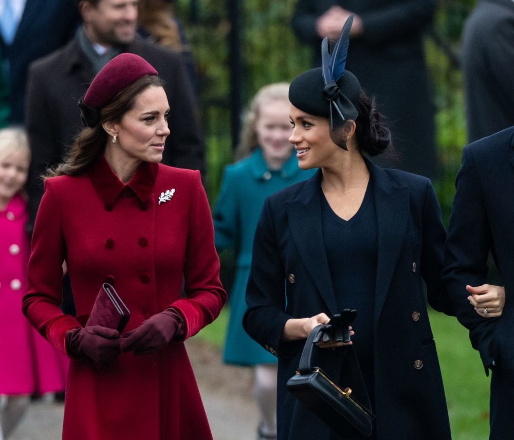 Kate Middleton y Meghan Markle conversando.