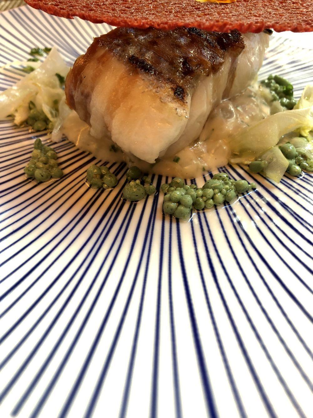 Merluza albardada en tocineta y falso risotto de hinojo al curry