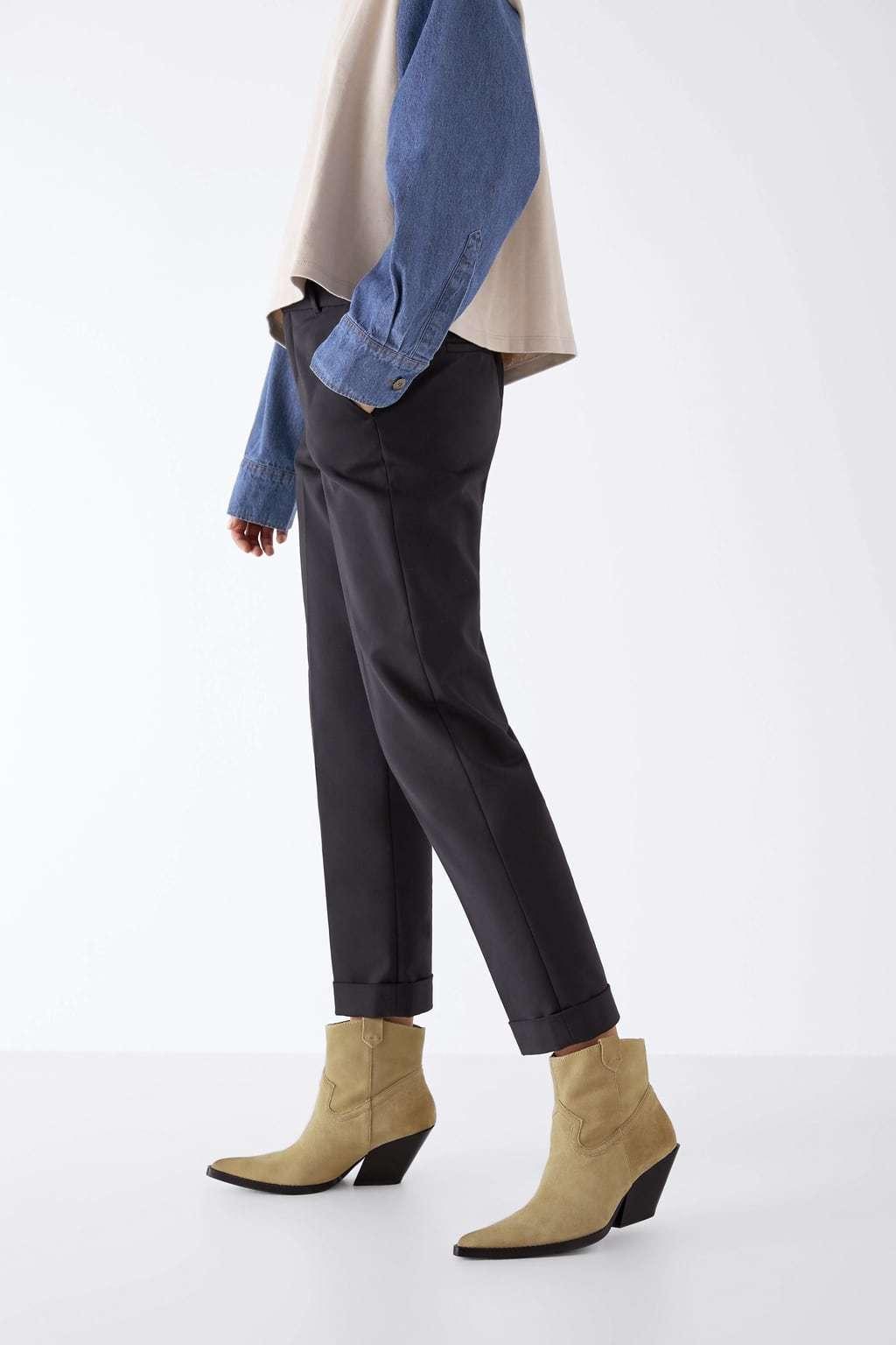 Botines de piel con tacón de color taupe, serraje con efecto envejecido en el corte y tacón cowboy, de Zara (59,95 euros).
