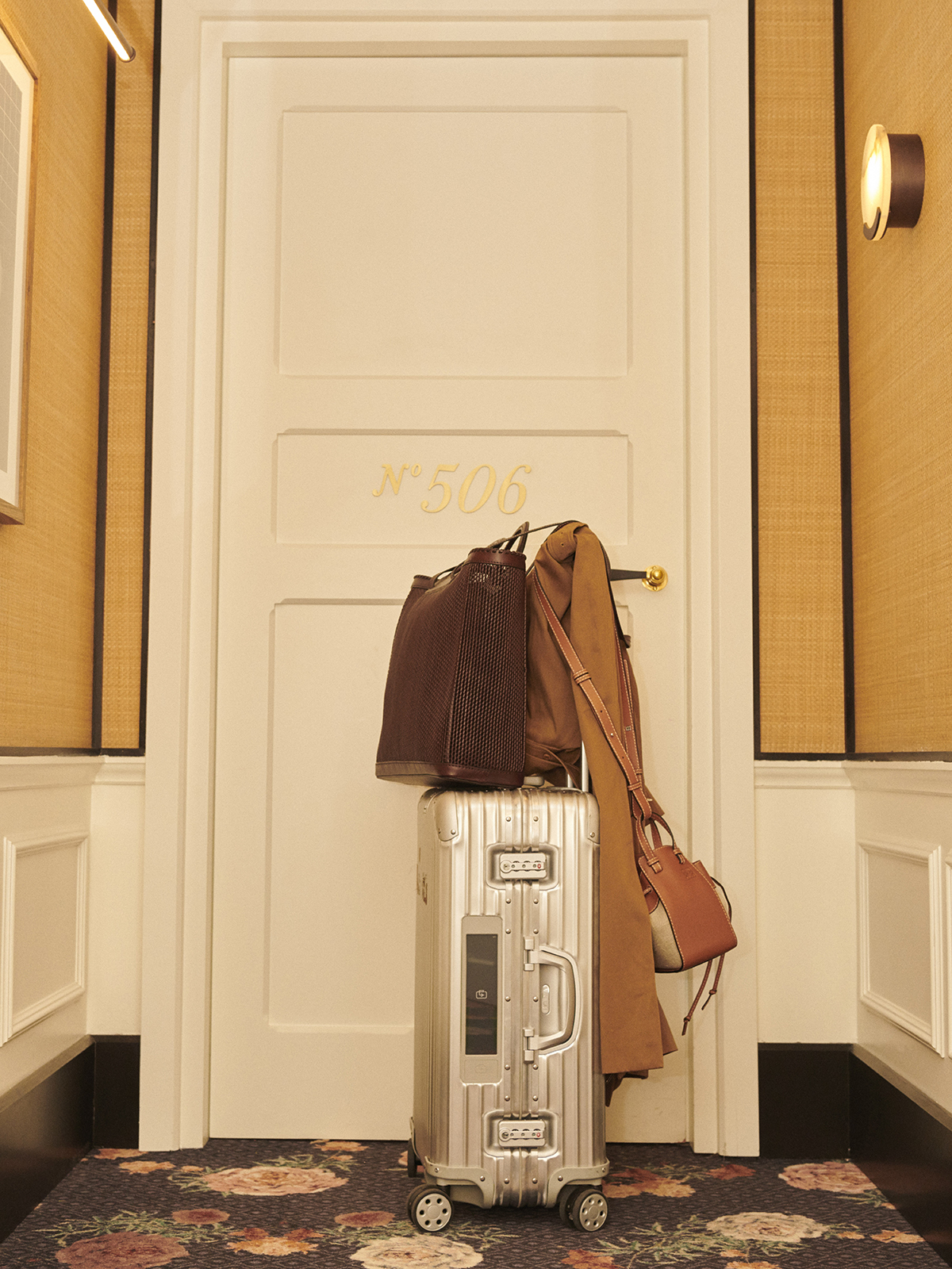 In the image, suitcase, RIMOWA; shopping bag and raincoat, MAX MARA and ...