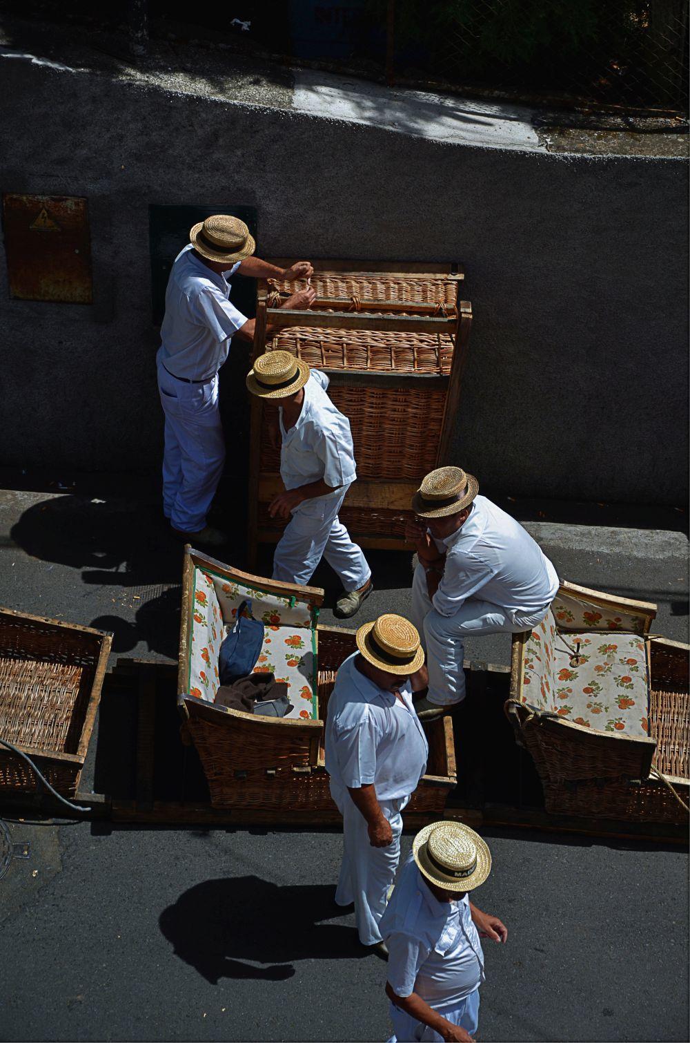 Los famosos carreiros llevan a los turistas colina abajo en cestas de...