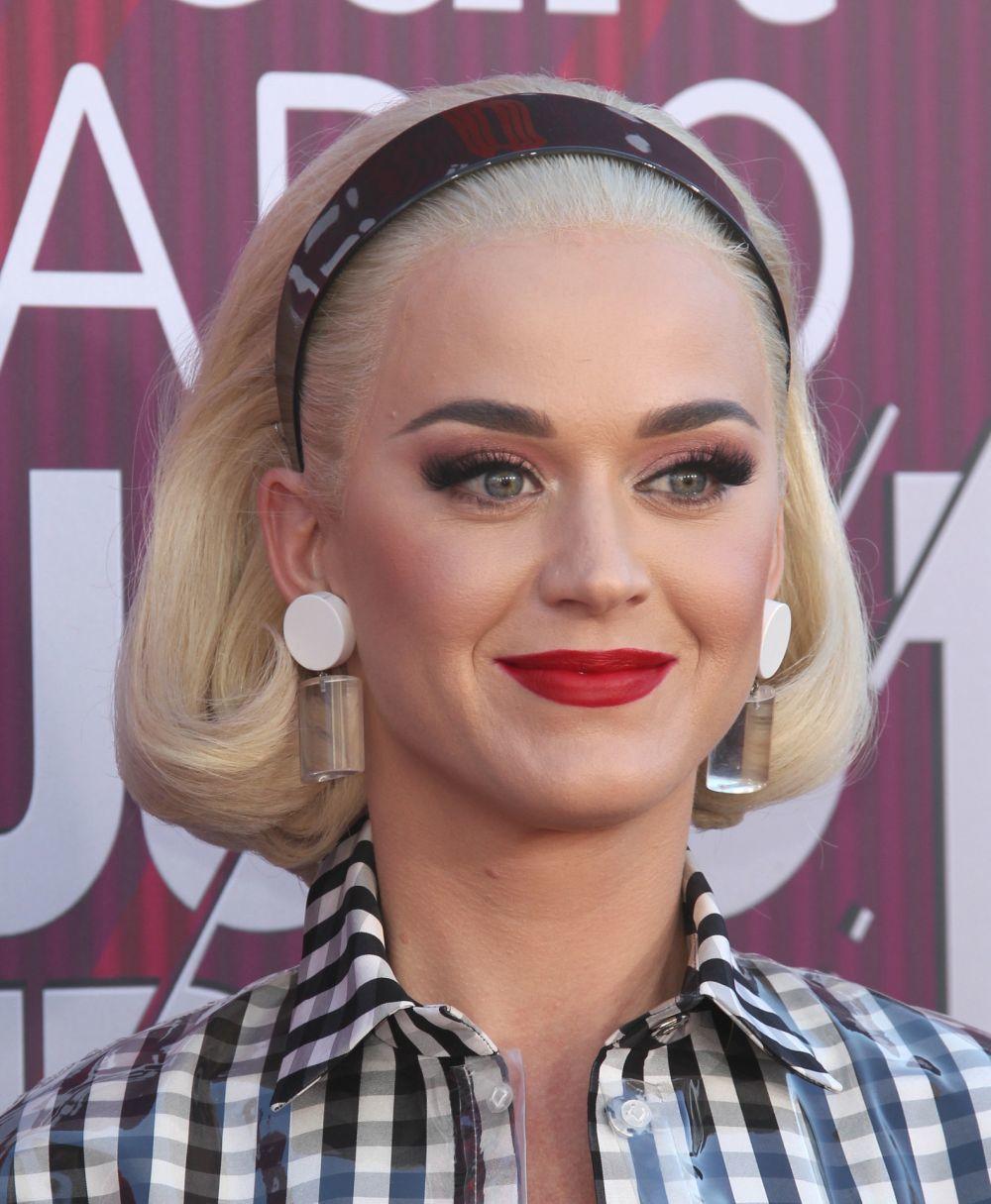 Katy Perry con diadema de charol con una melena muy años 60, rubia platino y maquillaje de labios rojos.