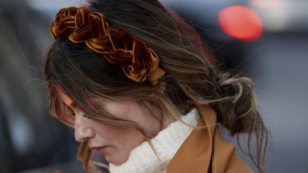 Para tus looks de aires boho y tu melena rizada o ondulada, nos encanta este recogido relajado con diadema de terciopelo trenzada que hemos visto en el street style de París.