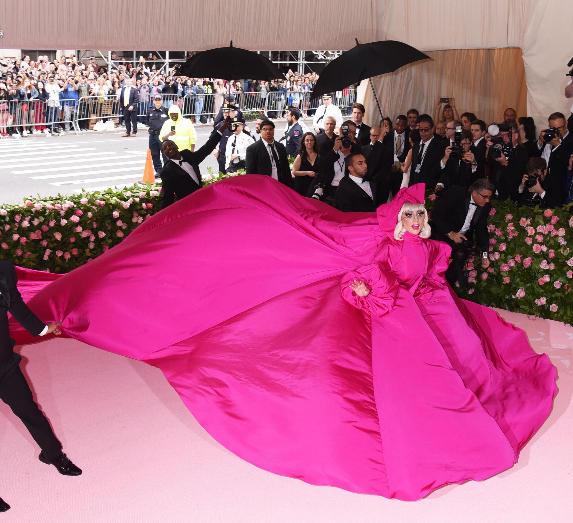 En su primer look, Lady Gaga lució un enorme vestido capa en fucsia...