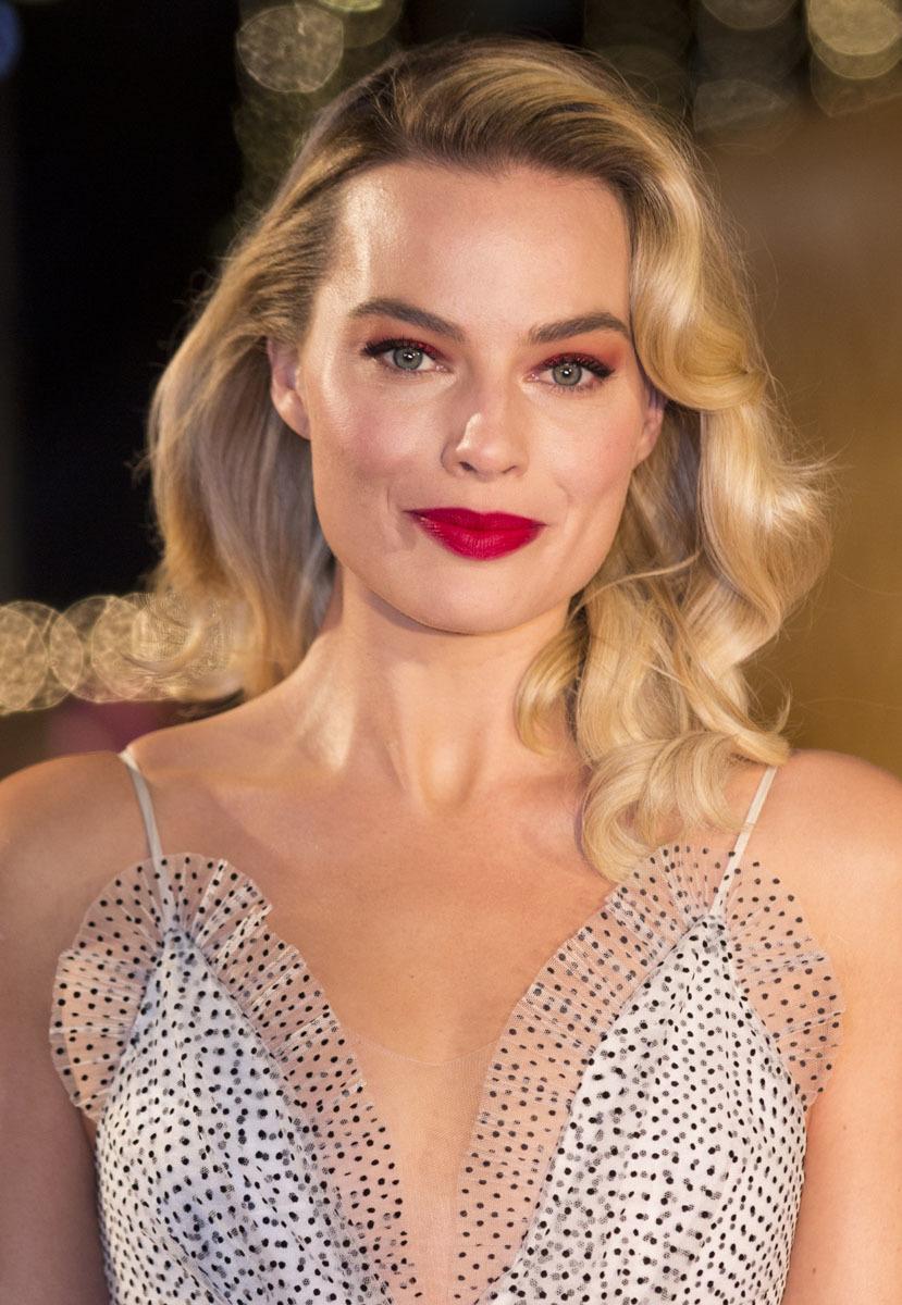 Margot Robbie con un maquillaje perfecto para una boda de tarde o noche con sombras en tonos rojizos y labial frambuesa.