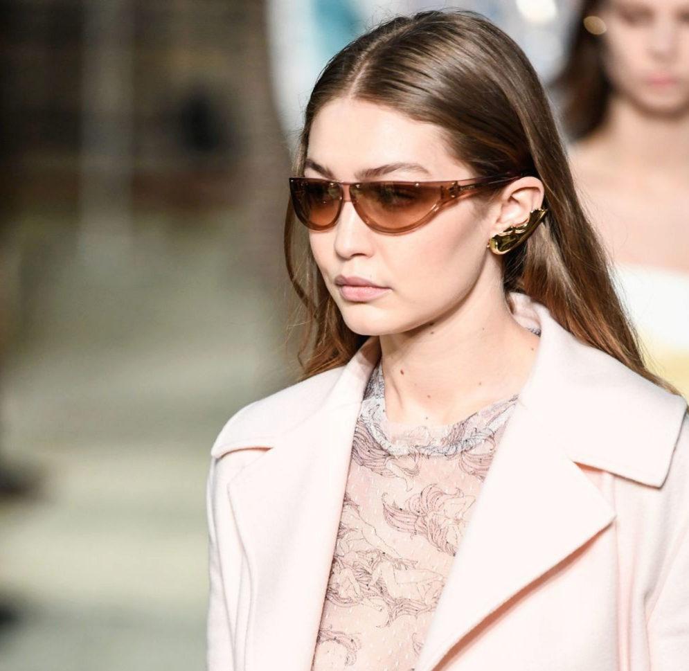 Gigi Hadid armoniza su rostro redondo con unas gafas de sol de montura superior recta.