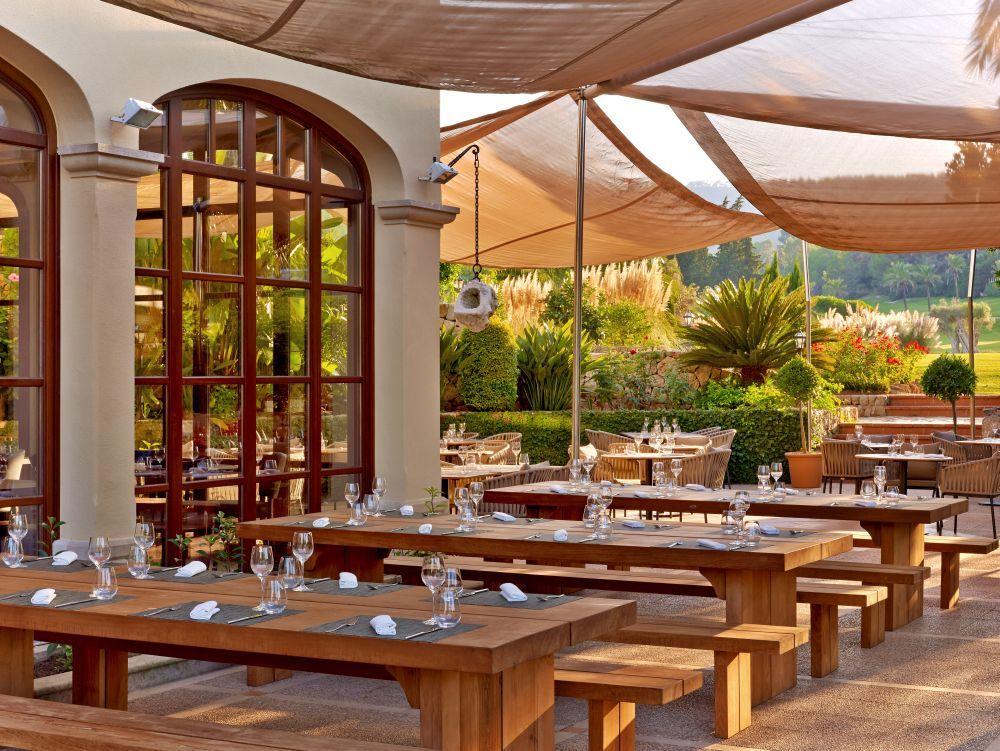 Restaurante informal de mesas corridas para comer con los niños junto a la piscina.
