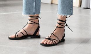 Sandalias minimalistas de piel llevadas con unos tejanos