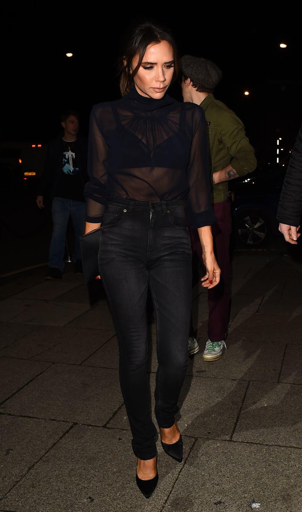 Victoria Beckham con jeans estrechos y una blusa con transparencias.