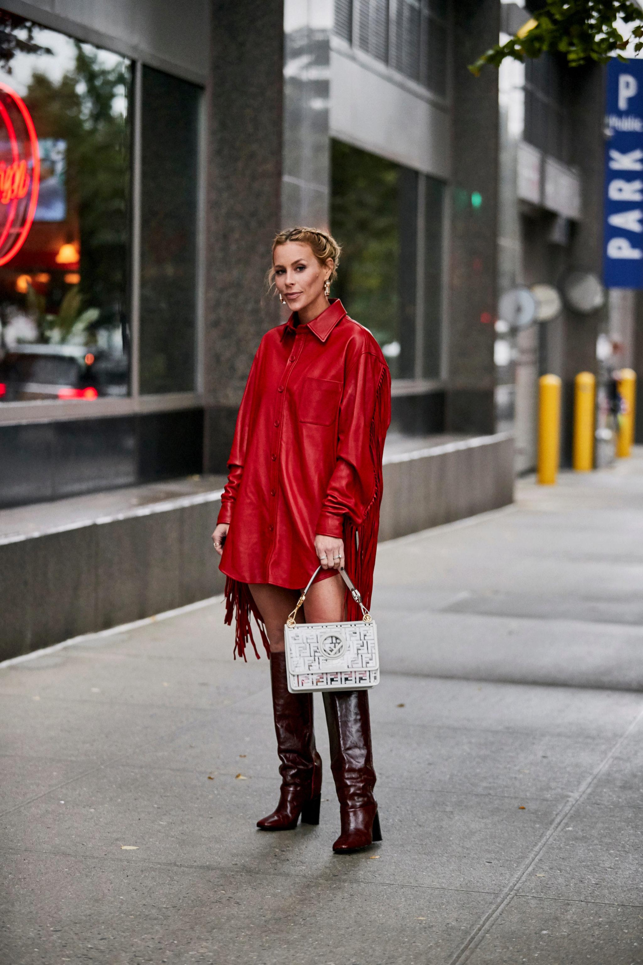 Cazadora de flecos en rojo con unas botas de piel en marrón chocolate por las calles de Nueva York