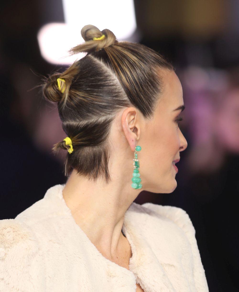 Sarah Paulson, que luce las mil posibilidades del pelo muy corto, con tres moñitos estilo japo con coleteros flúor.