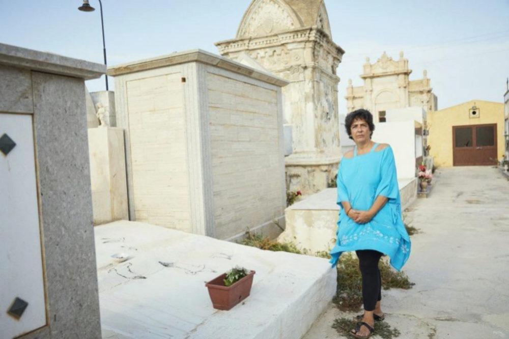 Paola La Rosa junto a la tumba de unos migrantes.