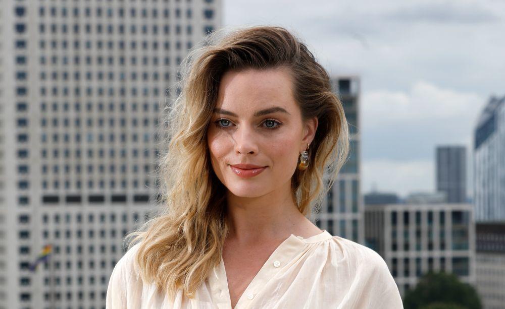 La actriz Margot Robbie con ondas surferas y un pelo suelto con volumen y movimiento.