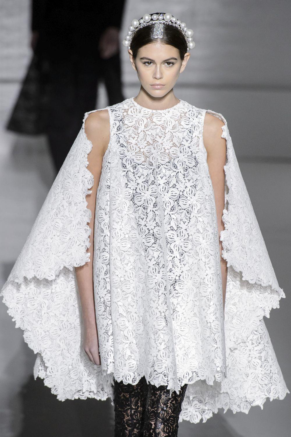 Kaia Gerber con un vestido de novia corto con capa, de Givenchy.