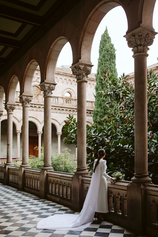 Margarita Gómez-Sala se casó con un vestido de Diego Estrada, con largo midi y capa y lo celebró en la Universidad de Barcelona.