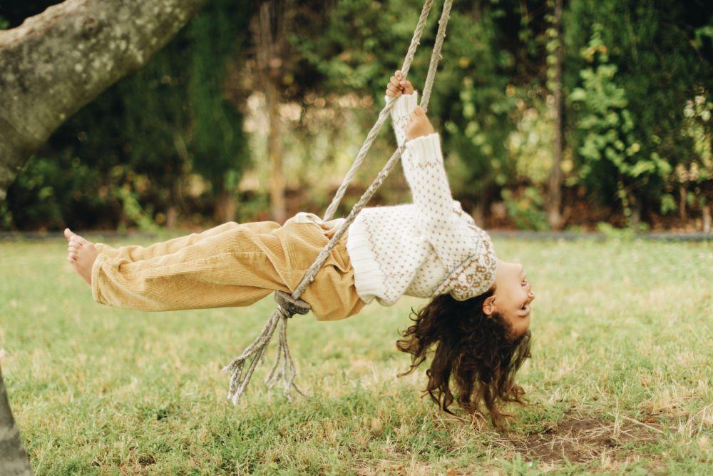 Los niños juegan al aire libre, en columpios hechos con cuerdas,...