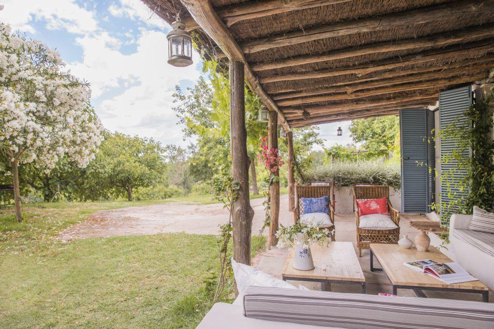 En el porche, mesas de centro de herrero y butacas con almohadones con...