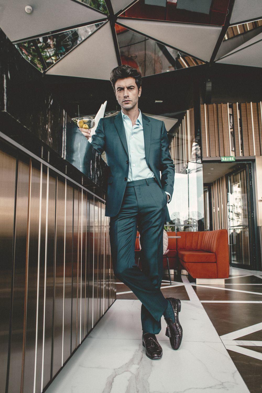 Javier Rey en el bar Ginkgo Sky Bar con traje de chaqueta en azul y camisa de traje azul celeste, de Christian Dior; calcetines en gris, de Scalpers, y slippers en marrón con borlas, de Jimmy Choo.