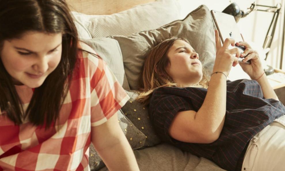 Dos jóvenes estudiando con dispositivos informáticos.