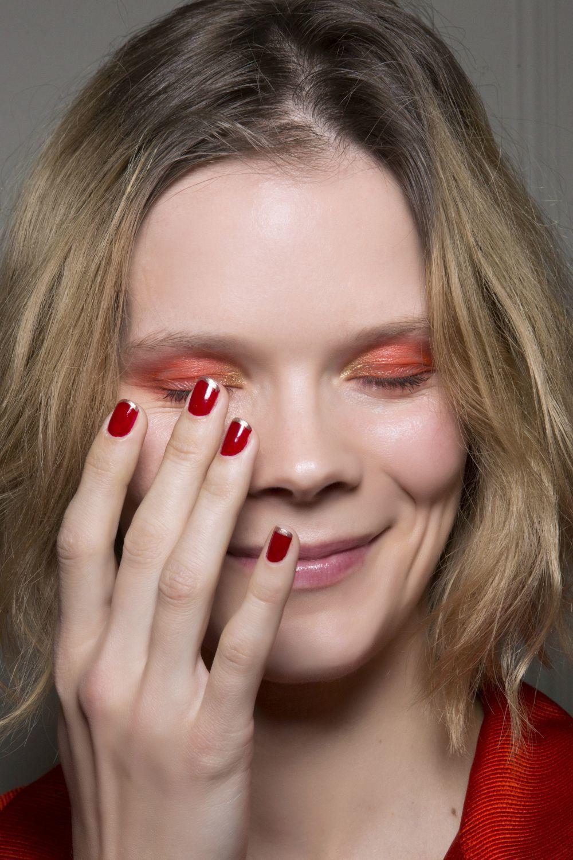 Manicura francesa de Leonard en rojo y dorado.