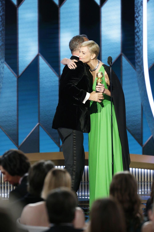 Charlize Theron le da el Globo de Oro a Tom Hanks.