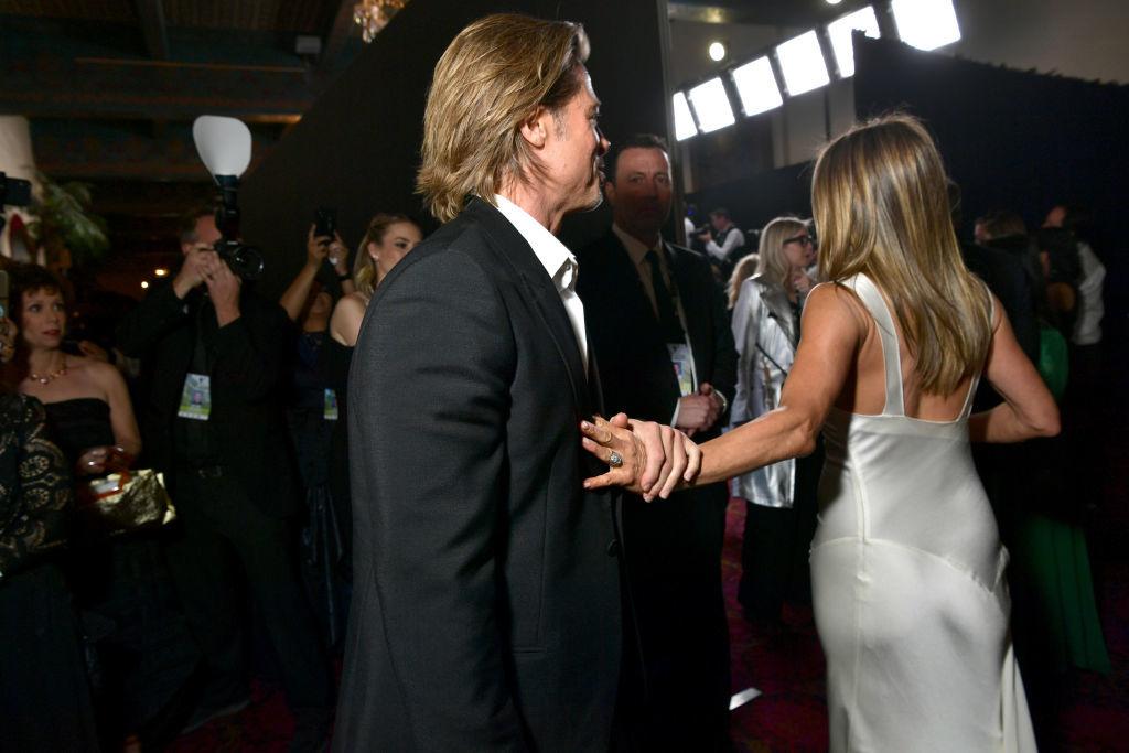 Brad Pitt le sujeta el brazo a Jennifer Aniston tras saludarse.