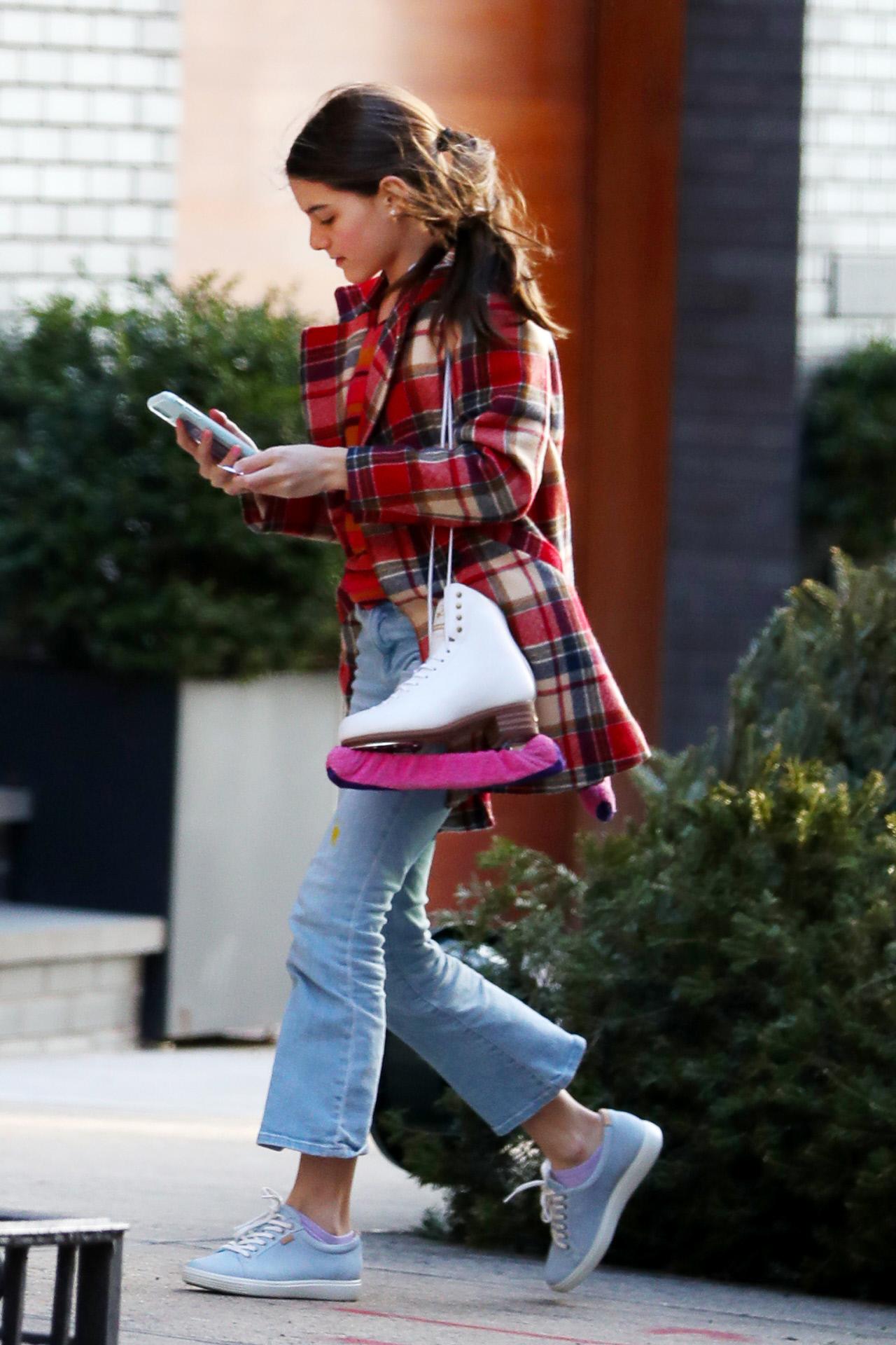Suri Cruise con abrigo de cuadros, jeans y zapatillas.