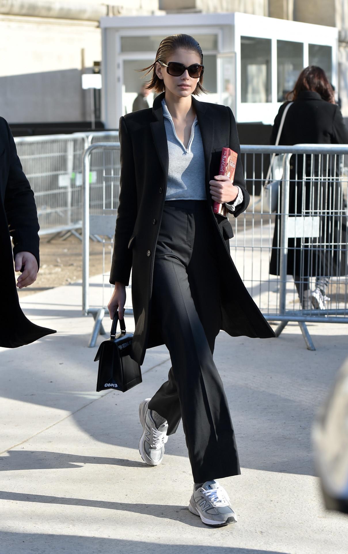 Kaia Gerber con pantalón de pinzas negro, abrigo tres cuartos y sus New Balance.