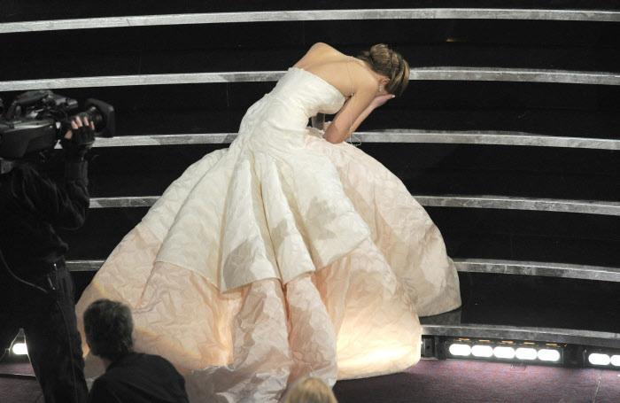 Jennifer Lawrence se cubrió el rostro cuando se levantó tras su traspié al recoger el premio como mejor actriz.