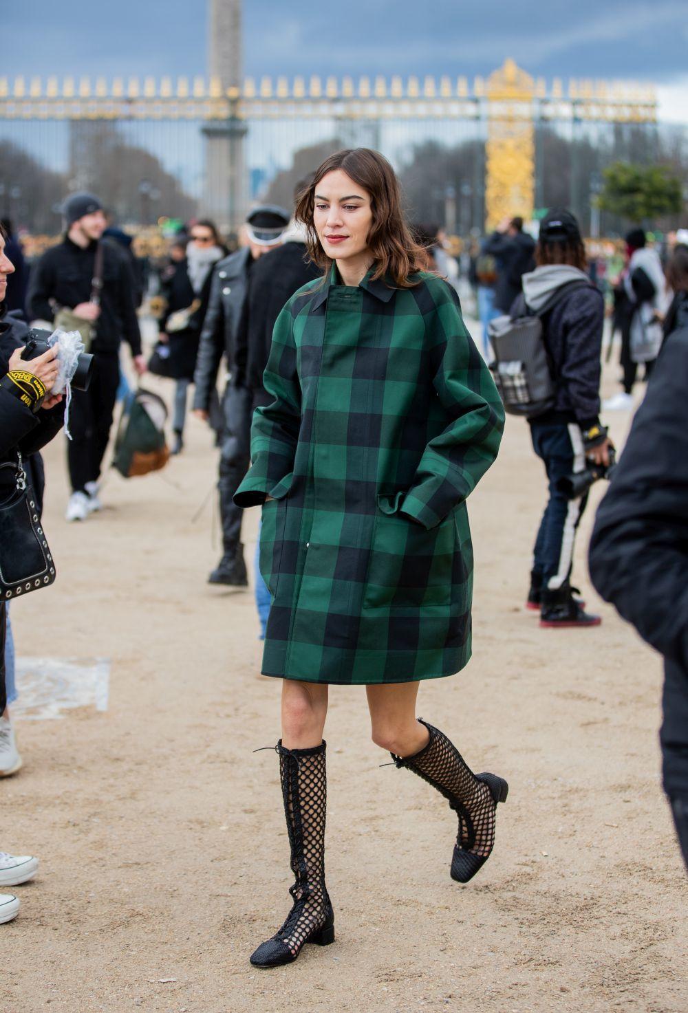 Alexa Chung con abrigo de Dior de cuadros y botas altas.