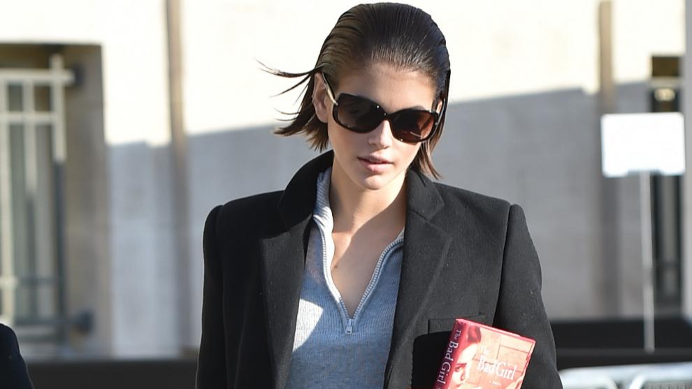 Kaia Gerber, libro en mano, durante la Semana de la Moda de París...