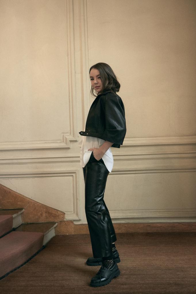 Alexandra lleva cazadora y pantalón en piel, camisa blanca, mocasines, y calcetines de red. Todo, Dior.