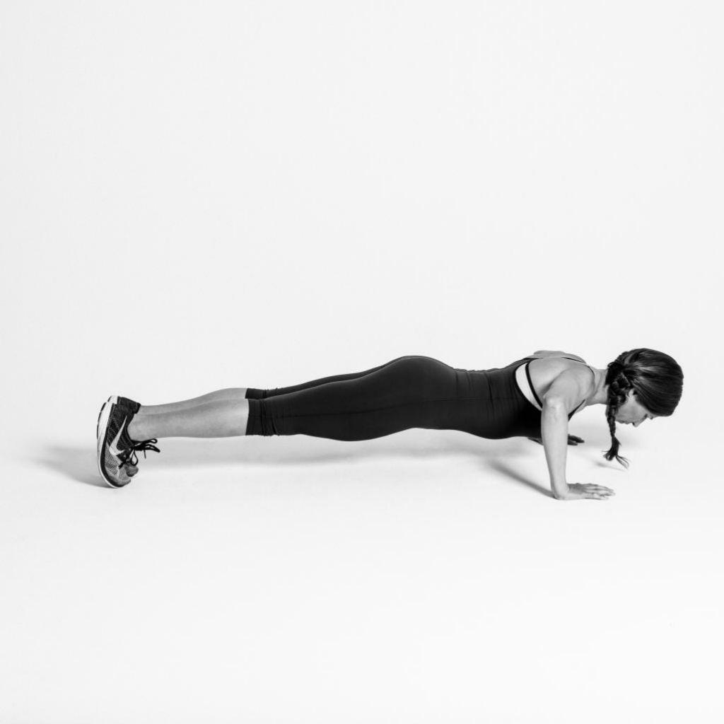 La entrenadora Carolina Prato hace fondos de pecho, flexionando los bazos y manteniendo la plancha.