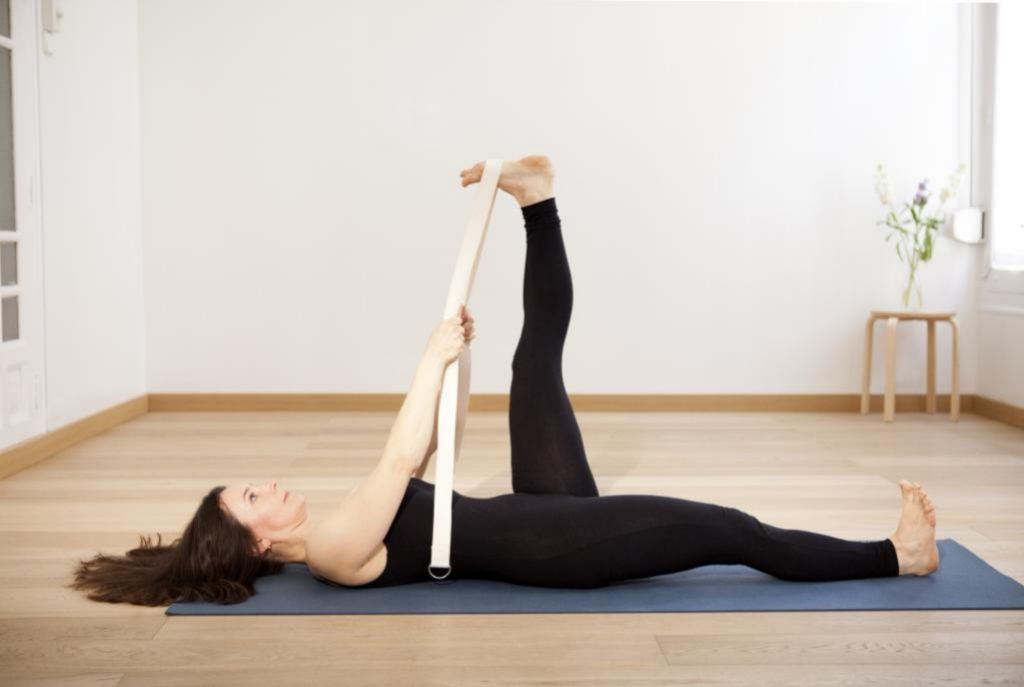 Elena Ferraris realizando un estiramiento de pierna con cinturón.