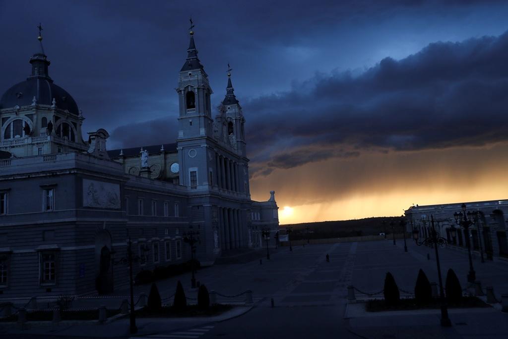 Un paseante solitario en la plaza vacía entre la Catedral de La Almudena y el Palacio Real durante el estado de alarma decretado para combatir el brote de coronavirus, en Madrid. Marzo de 2020.