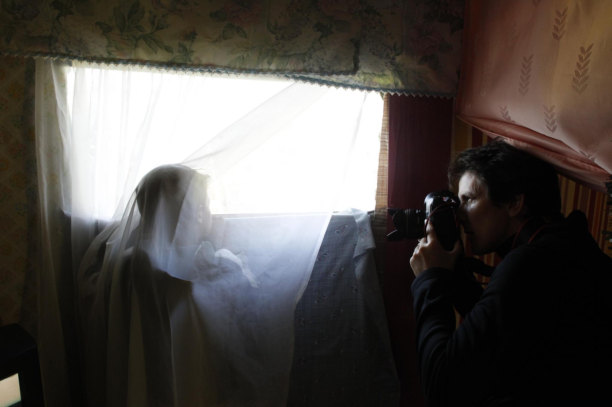 La fotógrafa Susana Vera saca fotos de un niño mirando a través de la ventana de su chabola en el antiguo asentamiento de El Gallinero a las afueras de Madrid
