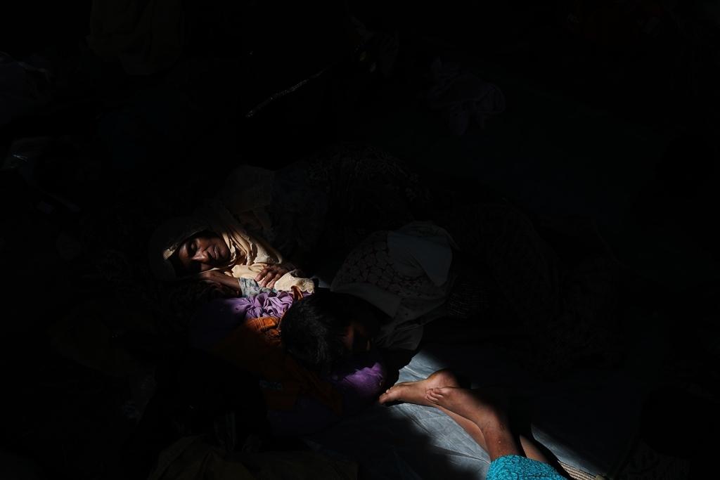 El refugiado rohingya Almor Yhan descansa con familiares horas después de cruzar la frontera entre Bangladesh y Myanmar el 23 de noviembre de 2017. Yhan perdió un hijo y dos sobrinos cuando su aldea fue atacada por el ejército de Myanmar. Después de que su hijo fuera asesinado, los soldados le arrojaron ácido en la cara y el cuerpo. Sólo pudo reconocerlo por la camiseta que llevaba puesta.