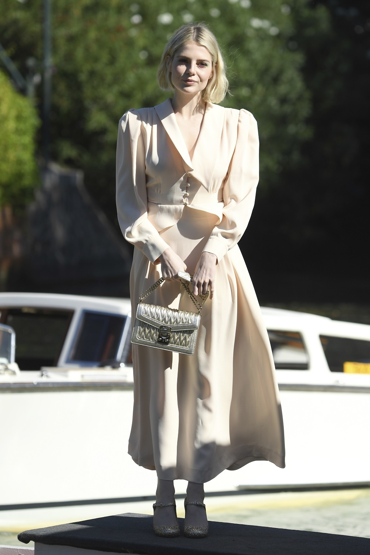 La actriz Lucy Boynton vestida de Miu Miu fuera de la pantalla.