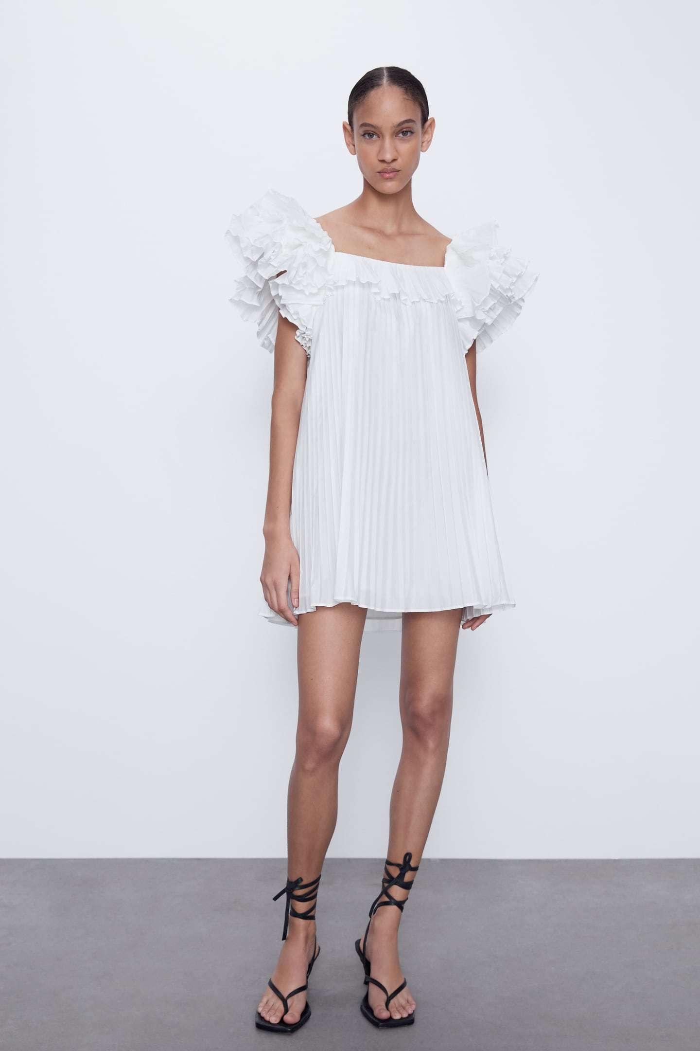 Vestido blanco plisado y con mangas con volumen, de Zara.