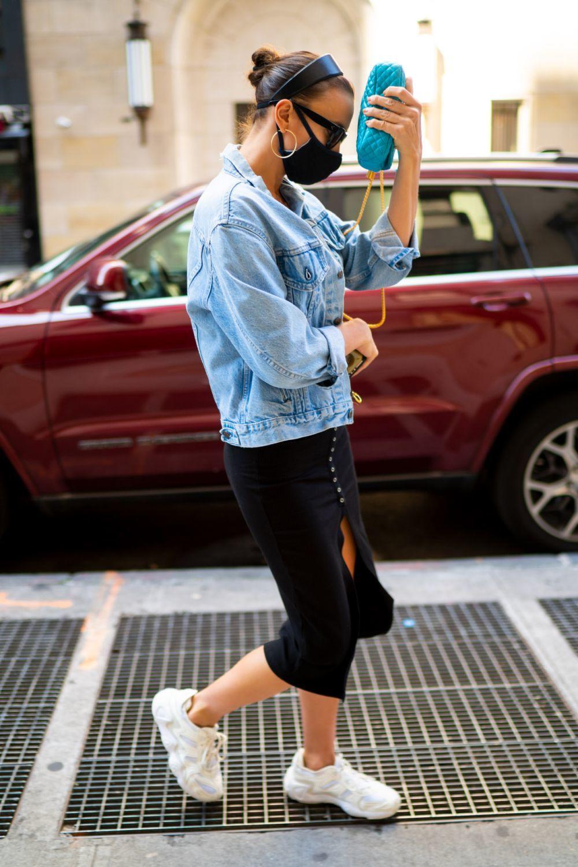 La modelo Irina Shayk en Nueva York con su último look con cazadora vaquera, falda midi y zapatillas deportivas.