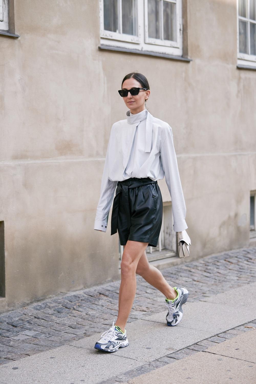 Short de piel con camisa oversize y sneakers.