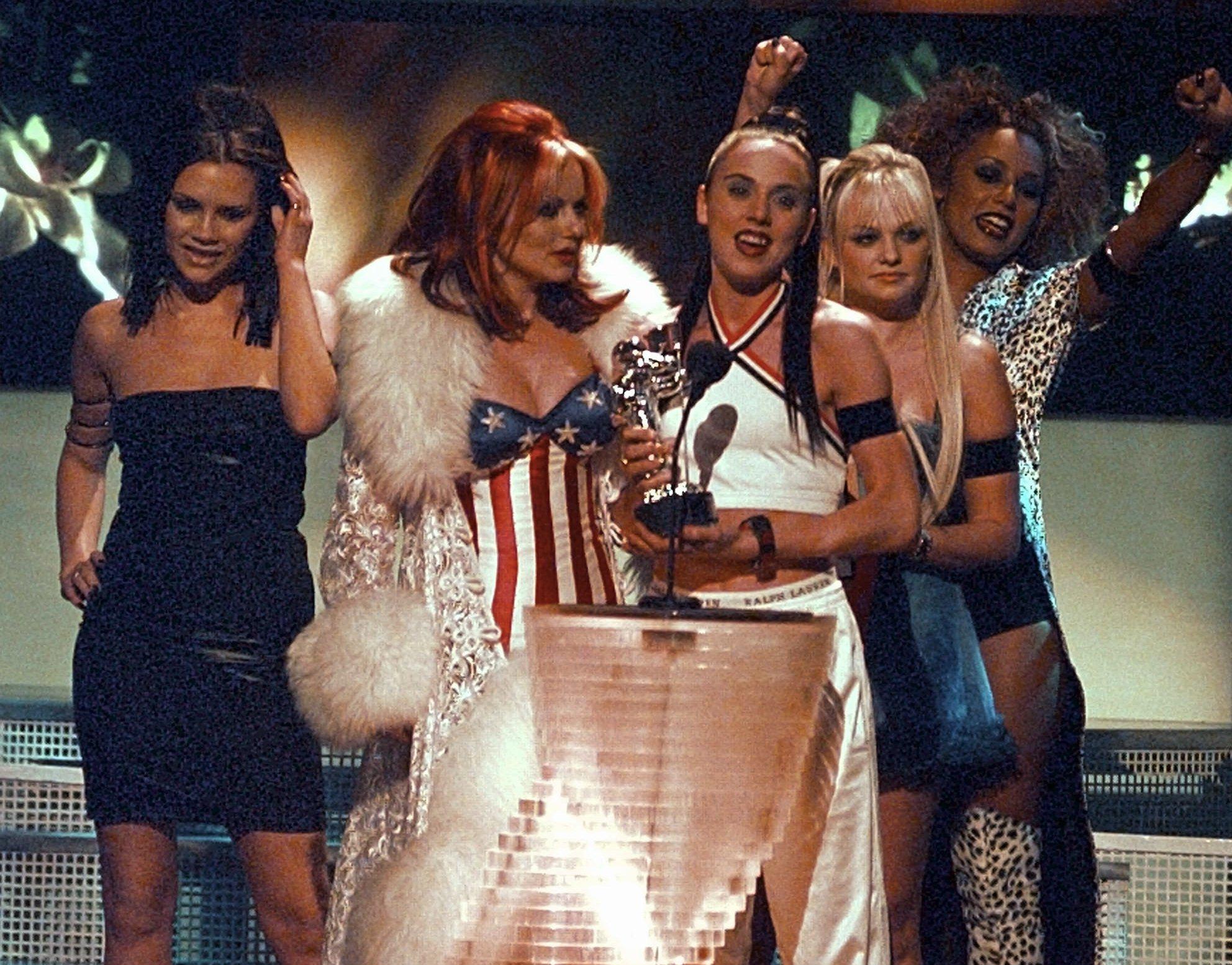 Victoria Beckham con su característico vestido ajustado negro junto al resto de las Spice Girls en 1997.