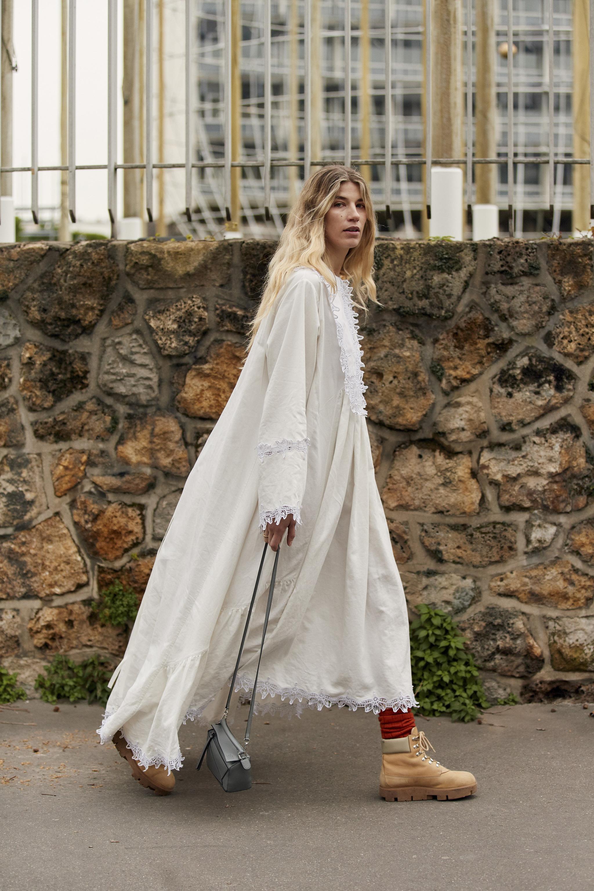 Veronika Heilbrunner con vestido blanco asimétrico y botas Panama Jack