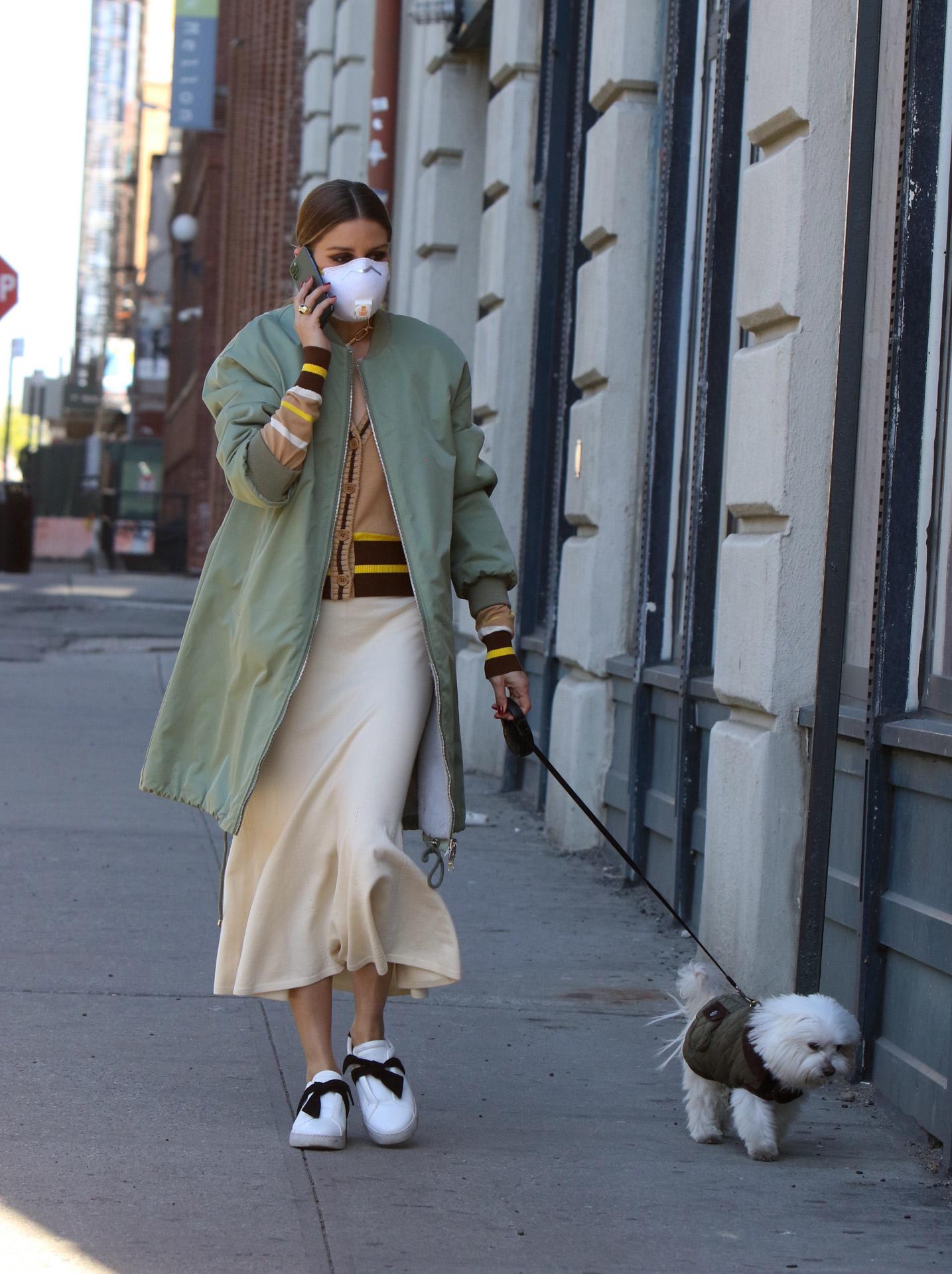 Olivia Palermo con un tres cuartos verde caza y falda midi con zapatillas.