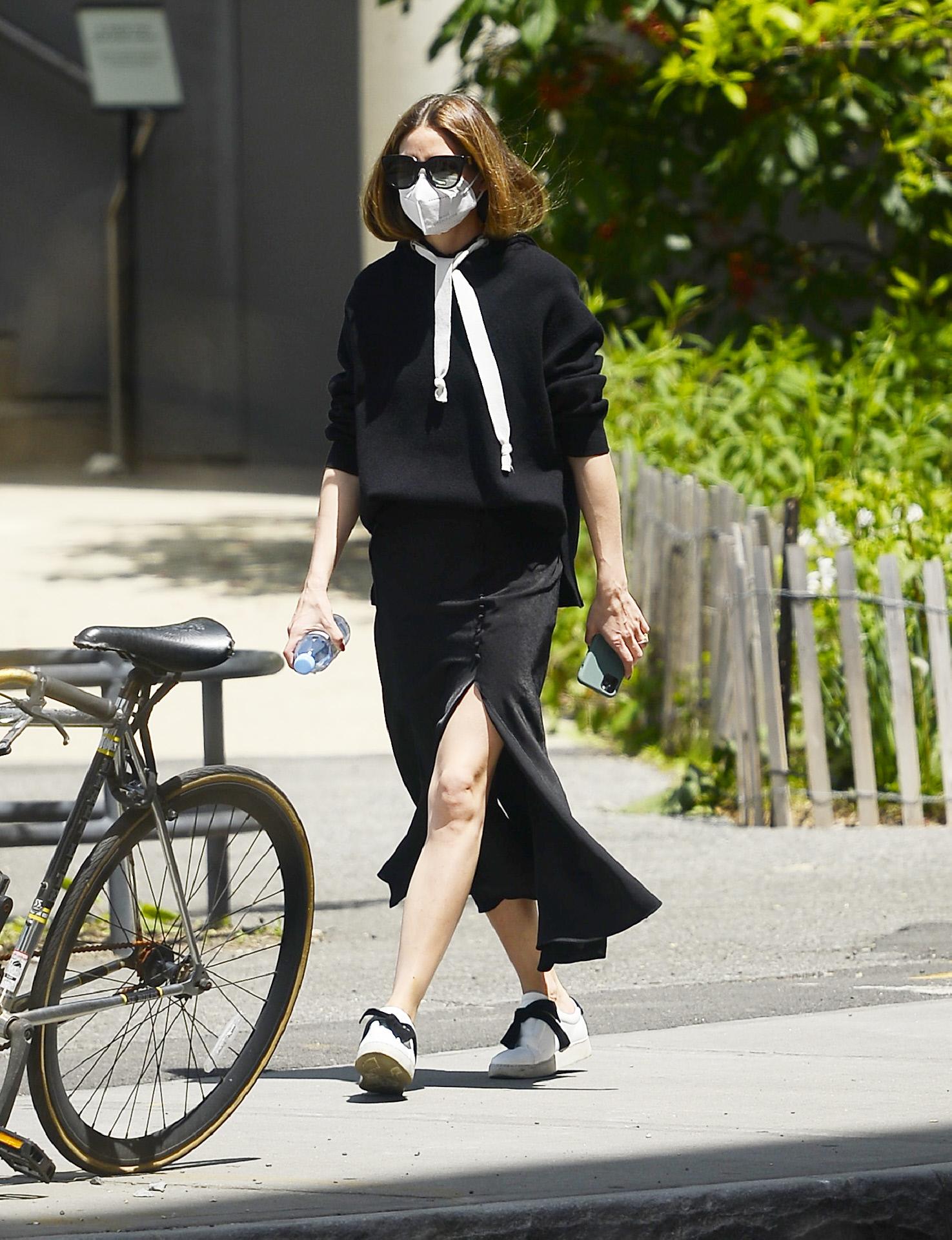 Olivia Palermo con sudadera, falda midi y zapatillas.